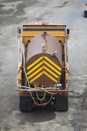 A specialized heavy duty truck transports dangerous chemicals in a marked tank.