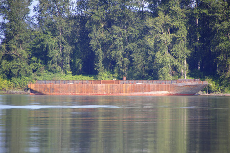 barge: A metal barge used for heavy industrial shipping on a river. Stock Photo