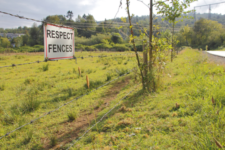 signage outdoor: A sign asks people to respect the fence