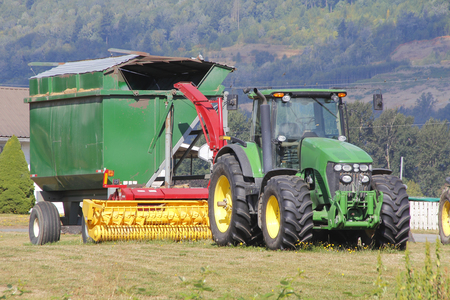 baler: Profile of a hay baler and tractor on a farm