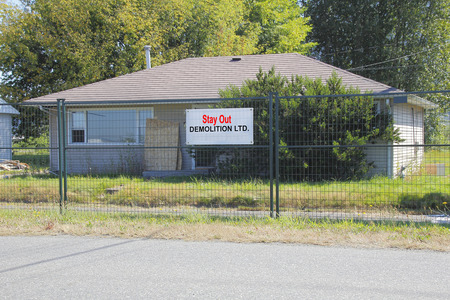home destruction: A house is surrounded by tall metal fencing prior to demolition.
