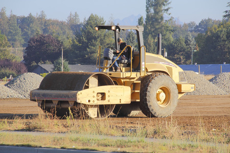 steamroller: An operator backs a steamroller over dirt to prepare for a construction site. Stock Photo