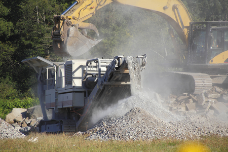 An industrial shovel loads rocks into a machine that crushes and piles the stone.