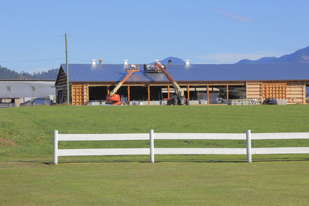 Construction workers install a metal roof on a large farm building.