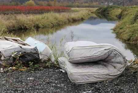 falta de respeto: Alguien muestra la falta de respeto por el medio ambiente descartando un colchón por un canal Foto de archivo
