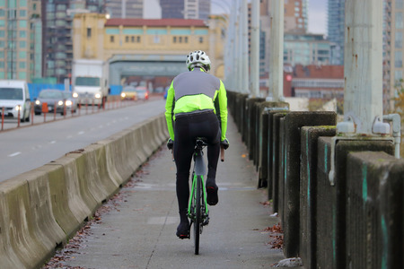 A cyclist commutes on his bike in a city. Stock Photo