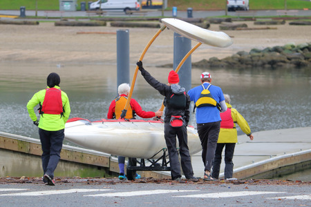 A five person team prepares to launch their scull boat with a long float into the waters.