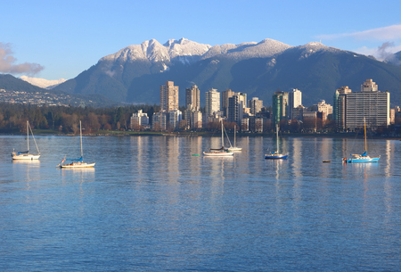 Sailboats on English Bay with Vancouvers Northshore Mountain range in the background on a winters day.