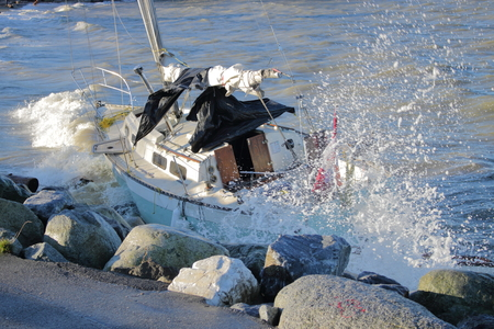 high winds: A sailboat is driven into the rocky shoreline by pounding waves driven by high winds.