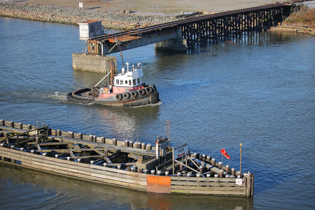 A tug boat navigates through a barrier created to direct river traffic safely.