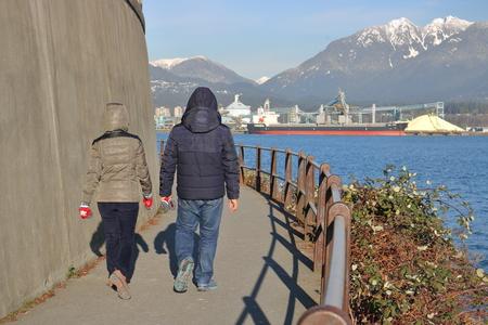 bundled: Bundled up for winter, a couple enjoy the diverse landscape on Vancouver, Canadas seawall.