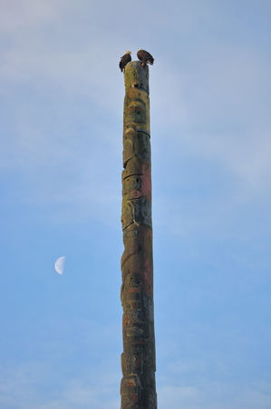 A pair of Eagles sit on top of a Canadian Native Indian totem pole accompanied by a half moon. Stock Photo