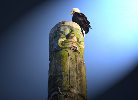 An eagle sits on top of a Native Indians totem pole illuminated by a shaft of light