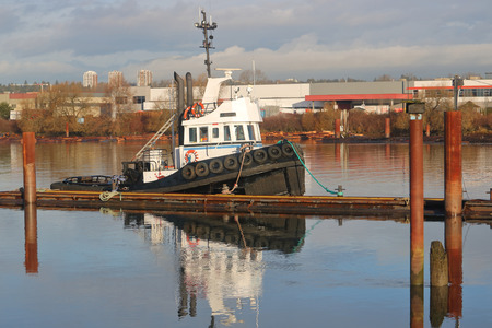fastened: An industrial tug boat used to haul heavy loads on the river is tied to a mooring pile. Stock Photo