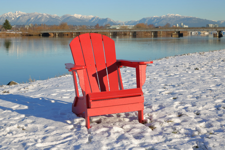A Traditional Bright Red Adirondack Chair Stands By The River During The  Winter Months. Stock