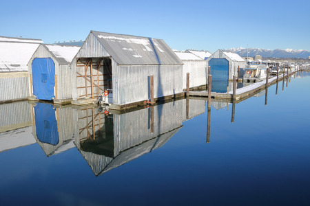A winter boat marina comprised of metal sheds on a glassy smooth and reflective river.