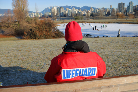 A Lifeguard ensures people are safe as they skate on a frozen city pond during winter. Stock Photo