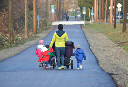 A babysitter or nanny takes her children for a walk.
