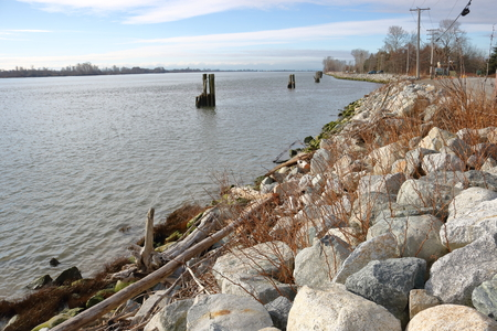 Heavy stone boulders are used to reinforce a dike