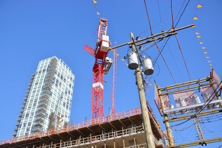 Towers, cranes, construction, utility poles and wires clutter a city skyline.
