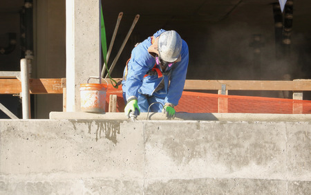 A construction worker uses a small, handheld sander for smoothing freshly laid cement.