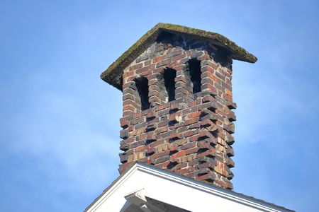 A tall, narrow red brick chimney with a peaked top.