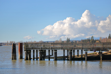 A wooden pier stretches out onto a river crowned with cumulus clouds.