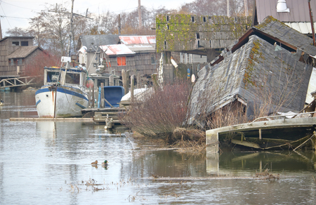 Squalor and old weather-beaten buildings comprise a shanty fishing village. Stock Photo