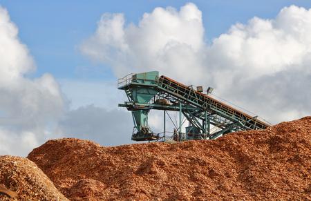 Een grote industriële transportband wordt gebruikt voor het stapelen en opslaan van houtsnippers. Stockfoto