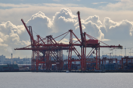 Cranes used for loading and unloading cargo onto ships is silhouetted against cumulus clouds. Stock Photo