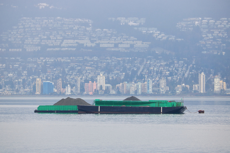 A flat barge used for transporting coal is anchored in Vancouvers English Bay. Stock Photo