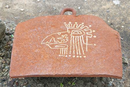 A modern Aztec figurine inscribed on a metal platform in an abandoned shipyard.