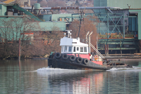 A working tug boat travels on a river occupied with industry.
