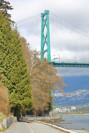 People enjoy a casual stroll under Vancouver, Canadas iconic Lions Gate Bridge on March 30, 2017.