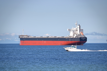 A speed boat races past the Valiant Summer, a commercial bulk carrier anchored in Vancouvers English Bay.