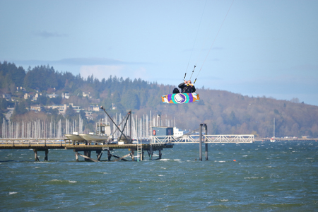 Kite Surfing on English Bay and, with the help of gale force winds, an avid surfer is launched high into the air in Vancouver. Canada on April 2, 2017. Editorial