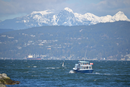 A small, local ferry heads out into open water with snow capped mountains in the background.