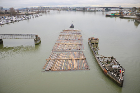 A tug boat successfully pulls 5 sections of log booms through a narrow passage on a river.
