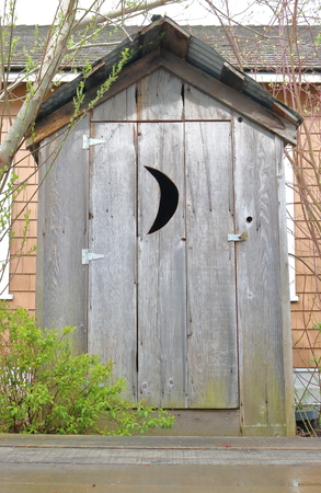 A traditional wood frame outhouse with a crescent moon on the door.