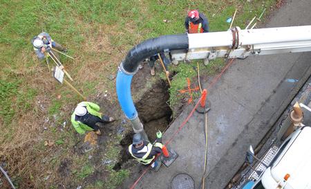 Hoge hoek weergave van een landmeter die werkt met een bouwpersoneel die een rioollijn repareert.