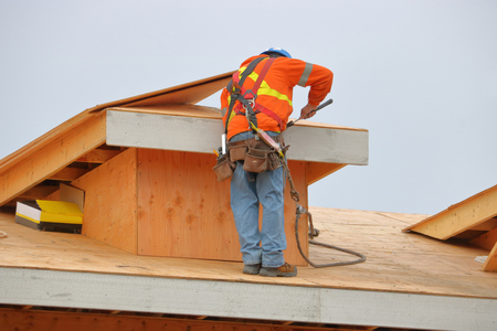 A tradesman hammers nails while working on a wood frame building.