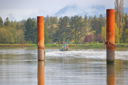 Tall and round, posts are used to secure barges and log booms on an active river. Stock Photo