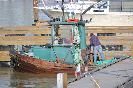 A tug boat operator secures his vessel in a marina
