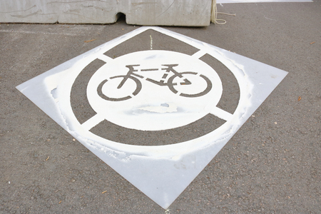 A stencil is used to paint a cycling emblem identifying a path for cyclists.