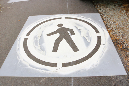 A stencil is used to paint an emblem identifying a path for pedestrians. Stok Fotoğraf