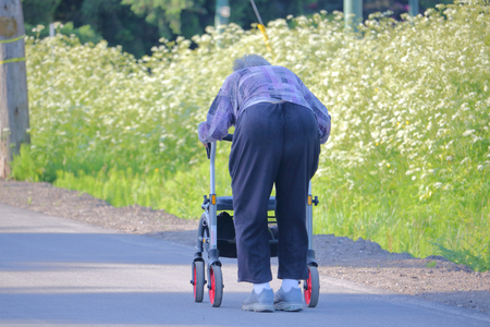 An old woman uses a walker to assist with her mobility.