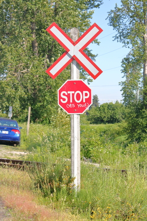 Someone has written an English message imploring people to stop at a rail crossing. Banco de Imagens