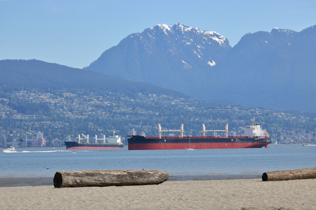 Large ocean freighters anchored near Vancouver, Canada waiting to deliver cargo.