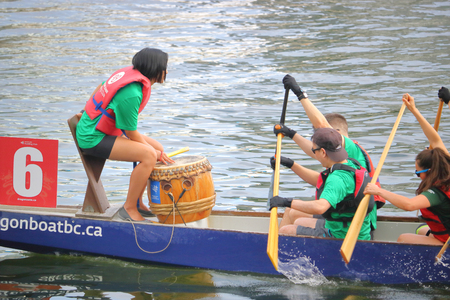A female dragon boat drummer or caller works with her team during competitions in Vancouver on June 11, 2017.