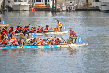 Dragon boats compete across False Creek during races held in Vancouver, British Columbia on June 11, 2017.